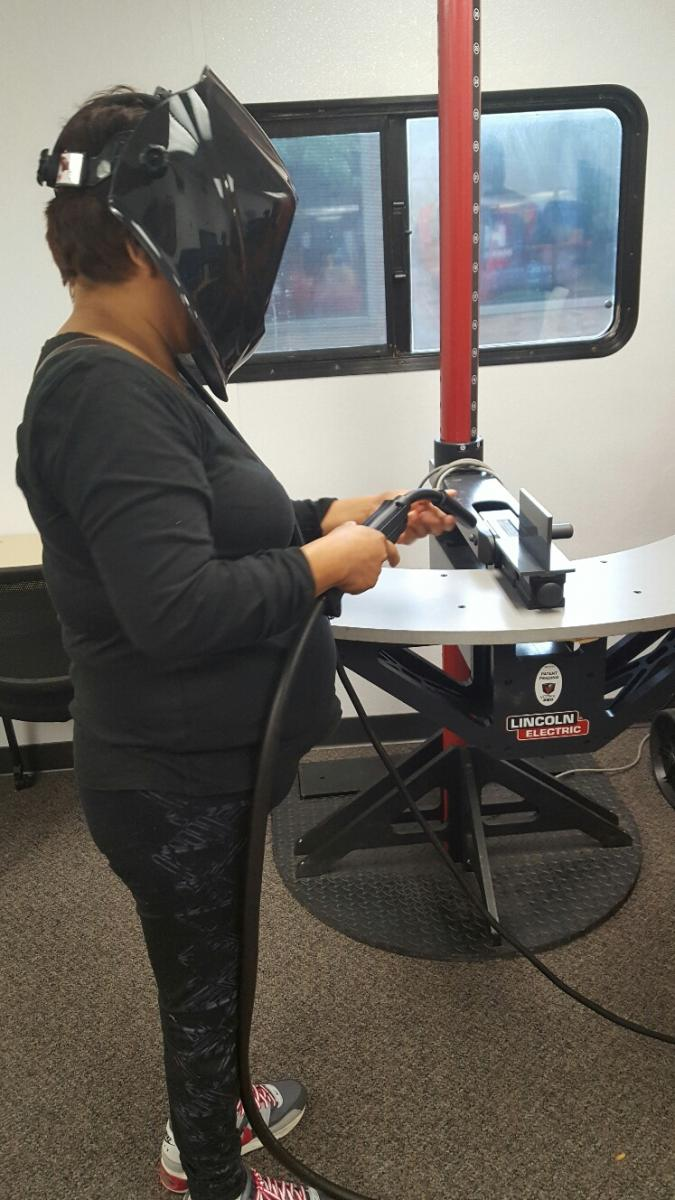 A woman tries her hand at a welding simulator.