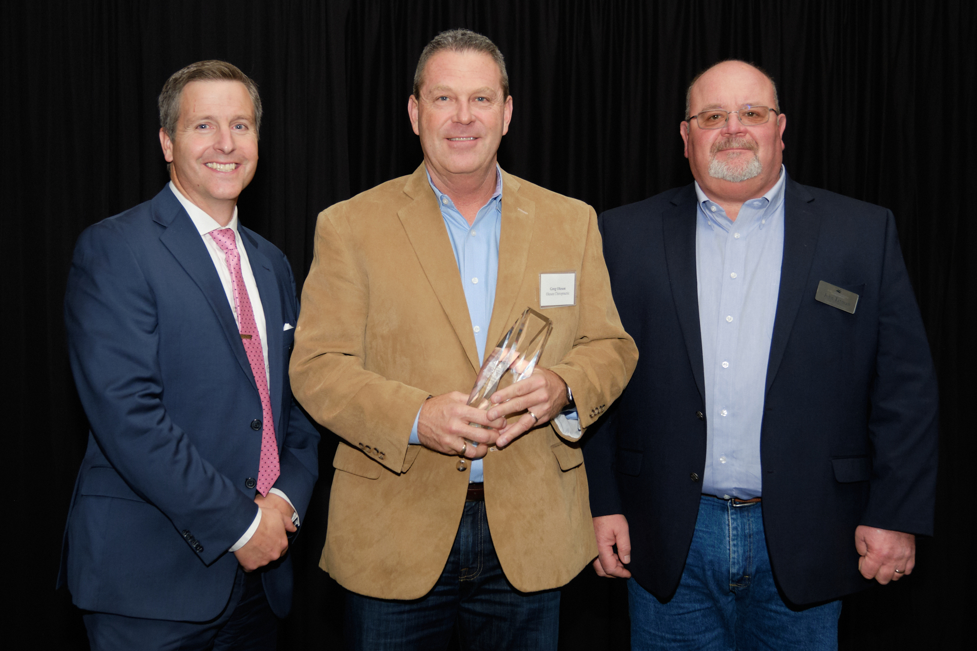 L to R: Corridor CEO Kiley Miller, Greg Oleson of Oleson Chiropractic - 2019 Small Business Excellence Awardee, Corridor Board Chair John Tatman