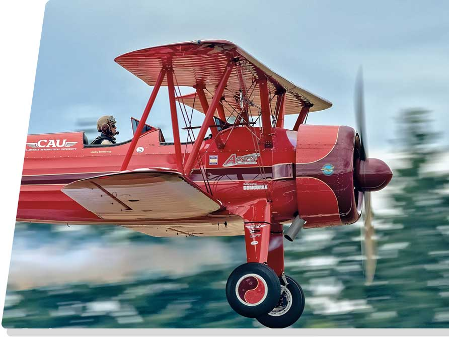 red biplane flying past pine trees