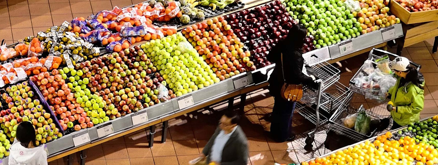 overhead view of shoppers in the produce aisle