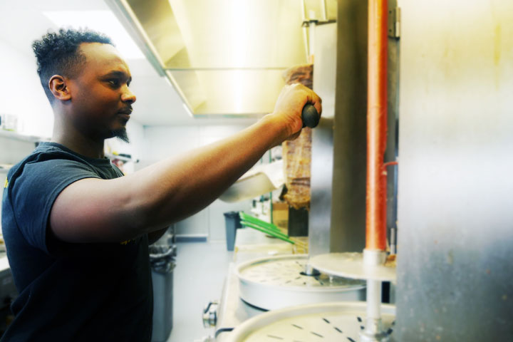 Abdi Ali works the deli counter in Karibu