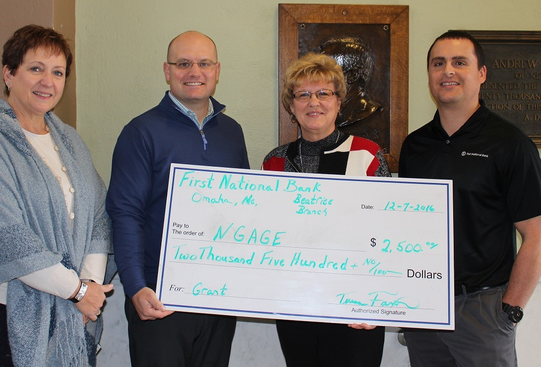 Walker Zulkoski and Glennis McClure of NGage accept check from First National Omaha reps Teresa Faxon and Heath Stewart